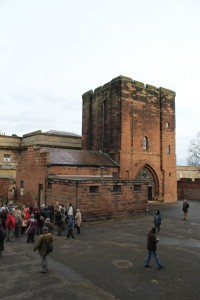 A crowd gathered in front of a reddish tower